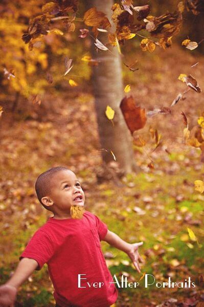 Smiling boy watching leaves fall.