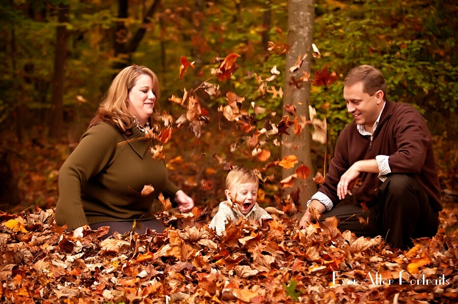 Happy family playing in leaves.