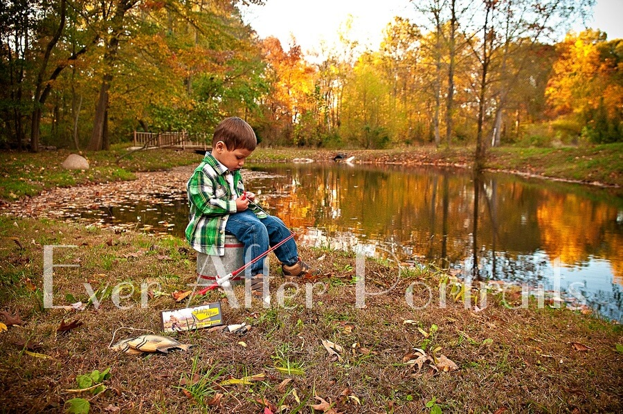 Little boy baiting hook on fishing pole at pond.