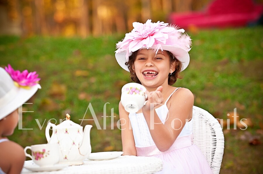With her charming smile, a girl enjoys playtime at a tea party.