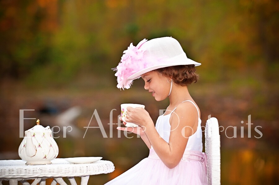 portrait photography Little girl with pink and white dress and hat holding teacup
