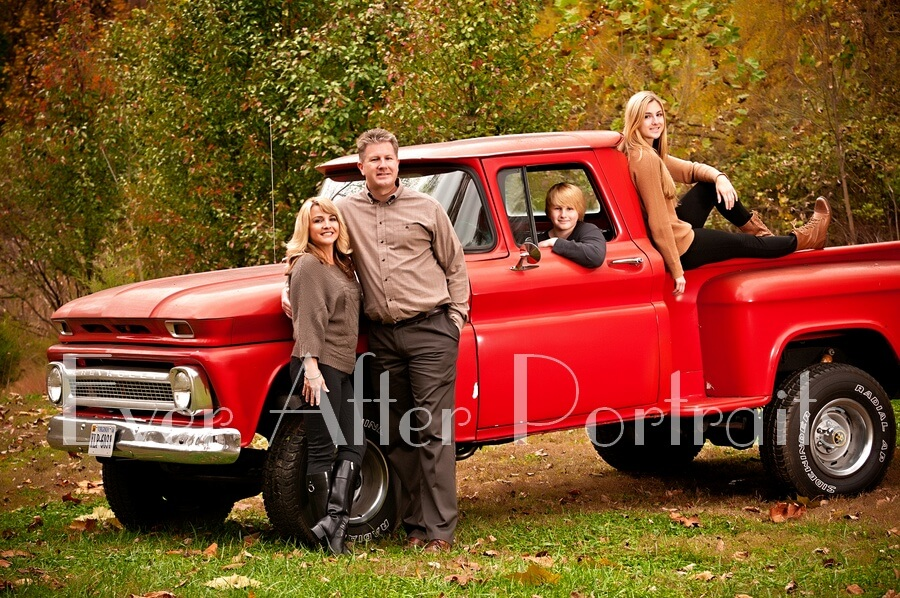Parents with children posing on red truck.