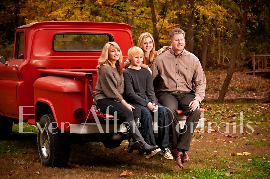 Smiling family sitting on back of red truck.