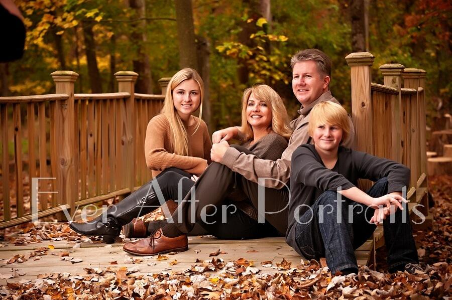 Happy family sitting on bridge.
