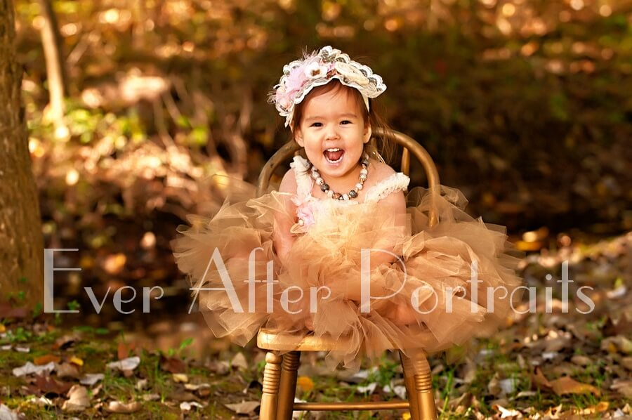 Two year old in beige tutu and floral headpiece.