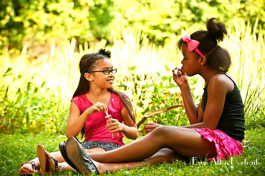 Two girls blowing bubbles.