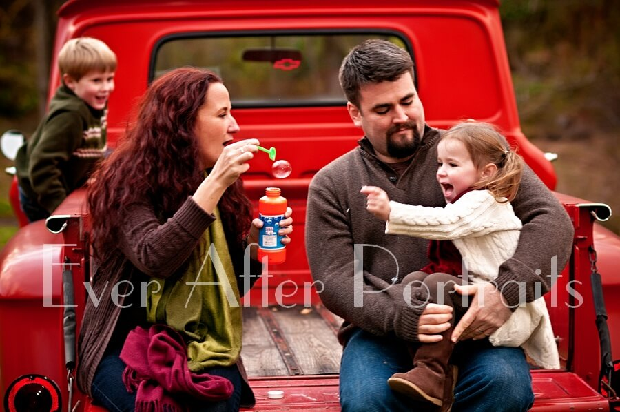 Family sitting on truck blowing bubbles.