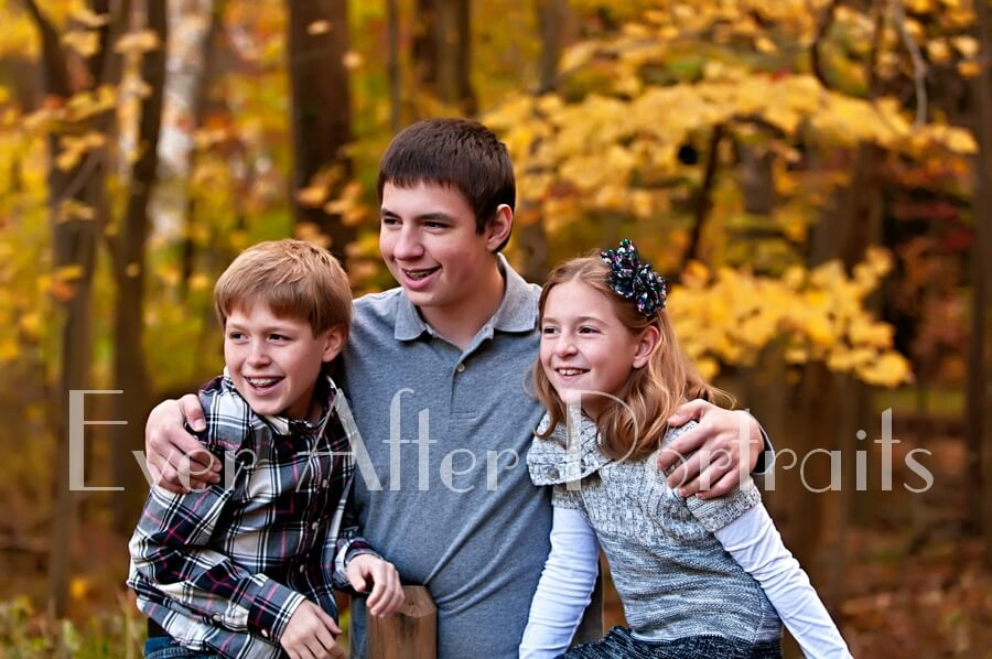 Brothers and sister in outdoor autumn image.