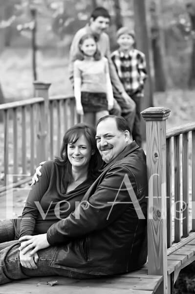 Parents sitting on bridge with three kids in background.