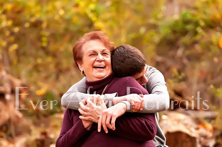 Grandson hugging grandmother in autumn photo.