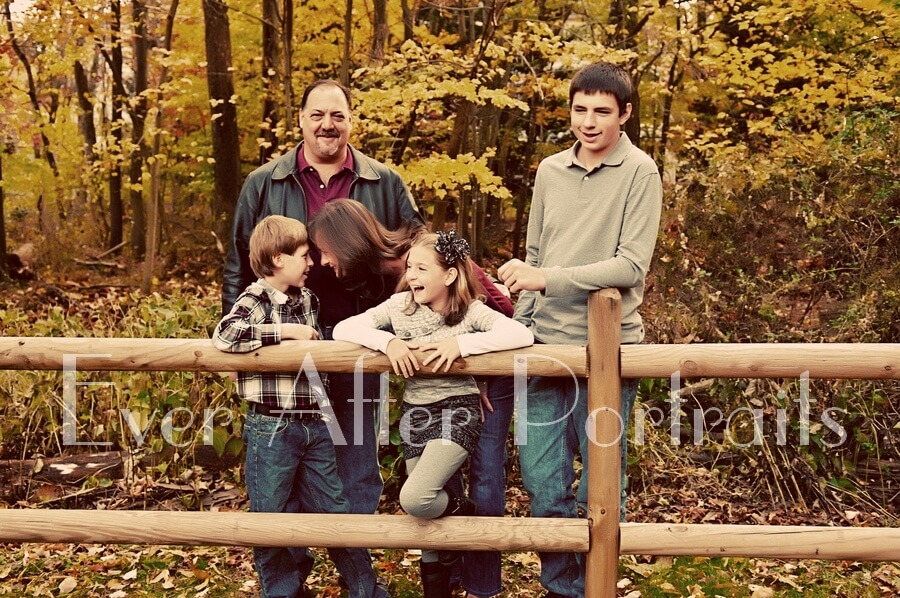 Family of five laughing at outdoor fence.