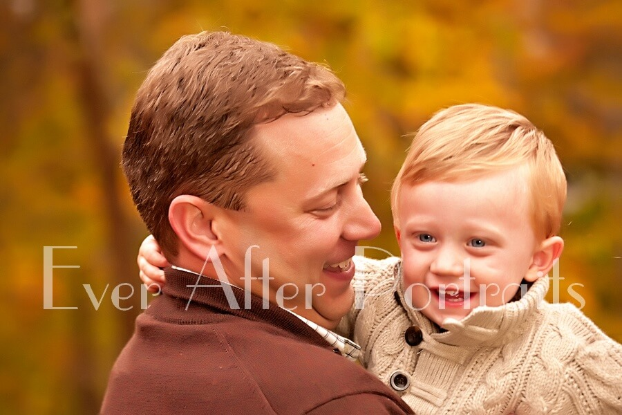 Father holding son in closeup image.