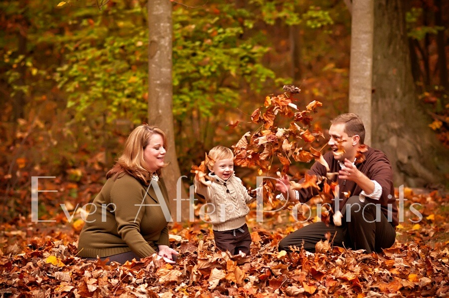 Family of three playing in leaves