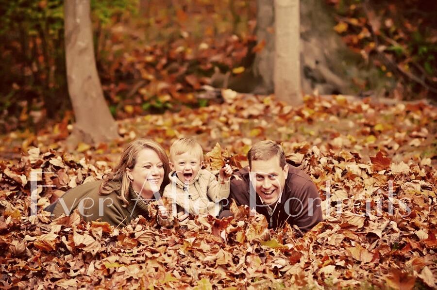 Family under piles of leaves.