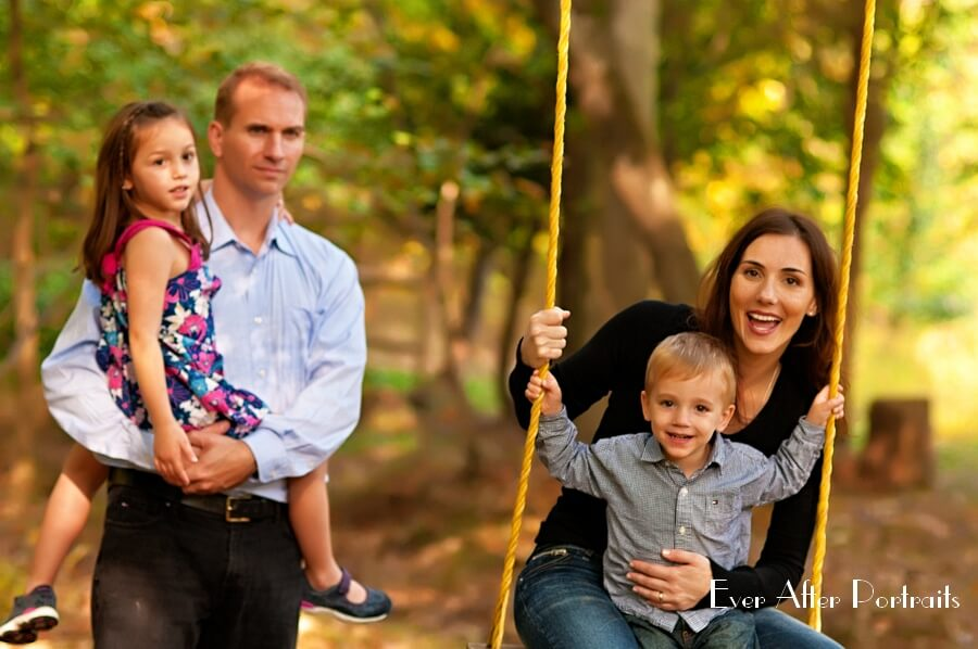 Laughing family playing on swing.