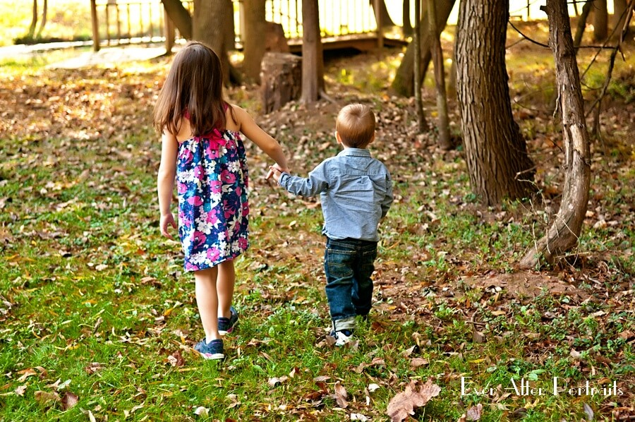 Brother and sister taking a stroll in the woods.