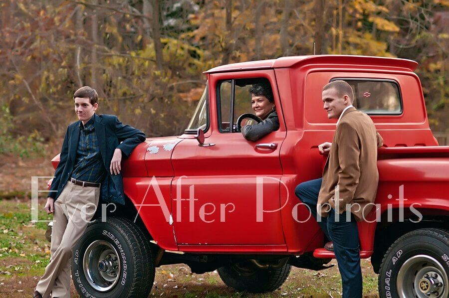 Family of three pose with red truck