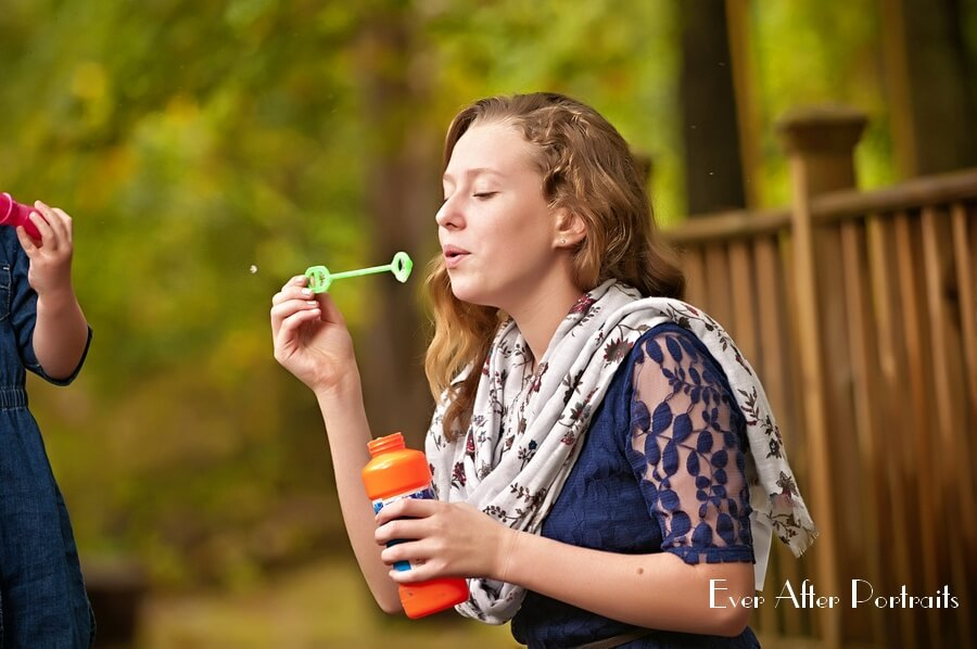 Teenage girl blows bubbles.