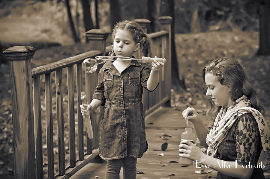 Two sisters blowing bubbles on bridge.