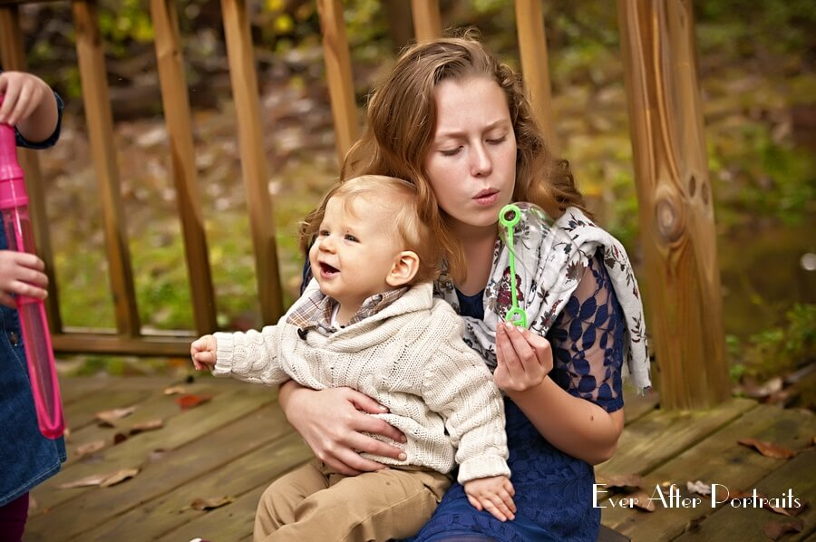 Big sister holds one year old brother.