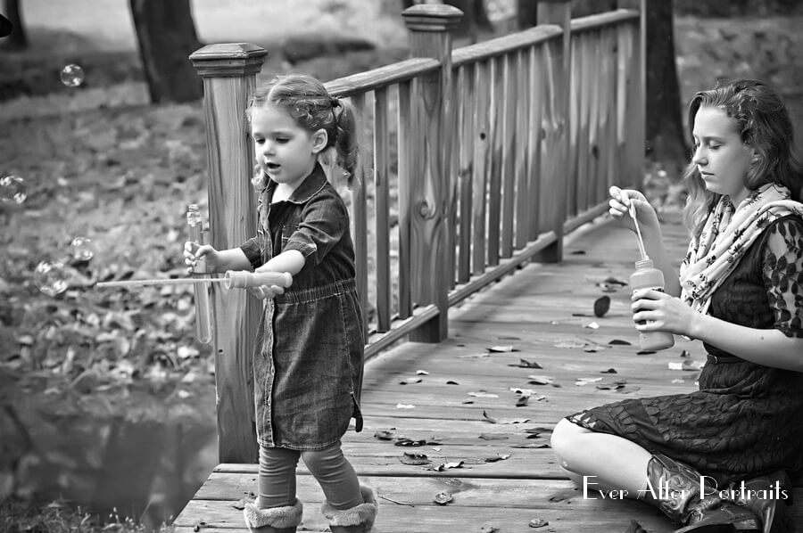 Siblings enjoy outdoors with bubbles.