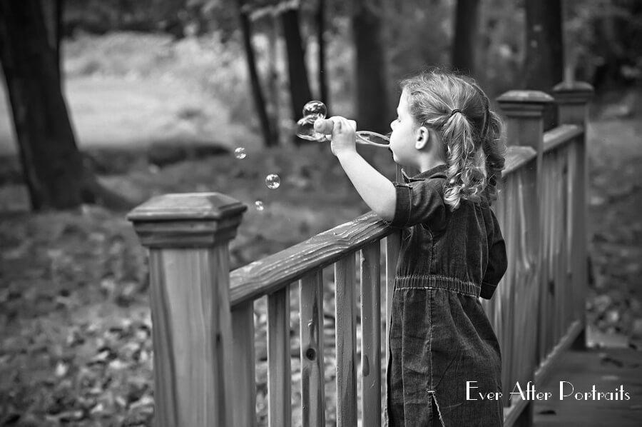 Little girl on bridge watching soap bubbles.