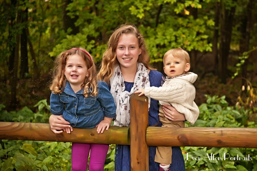 Two sisters with baby brother in outdoor image.
