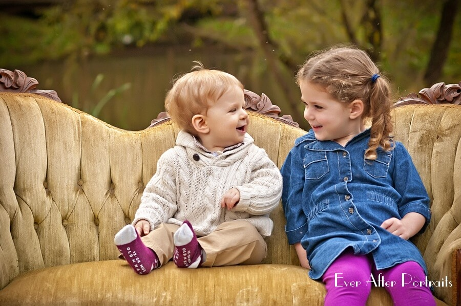 Young siblings on sofa in outdoor portrait.