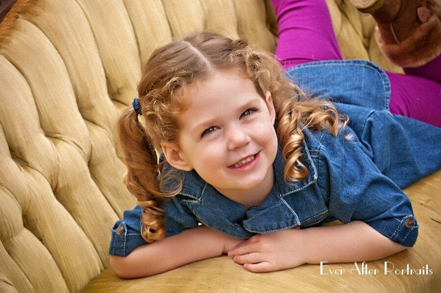 Little girl with pigtails on gold sofa.