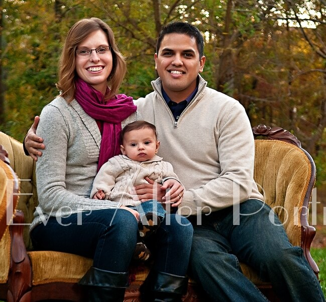 Parents with baby boy  in sofa portrait.