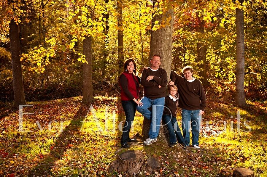 Family posing next to tree in autumn.