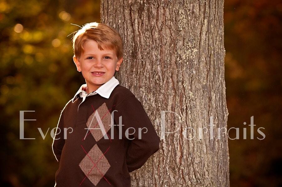 Boy standing next to tree.