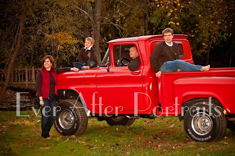 Family posing by red truck in autumn.