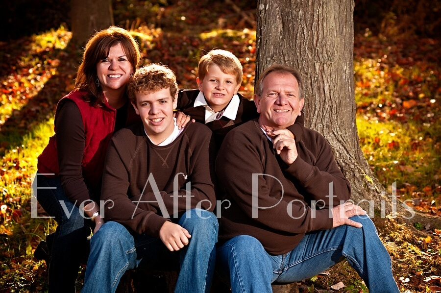Family of four in autumn outdoor image.