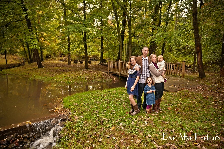 Parents with three children in the woods.