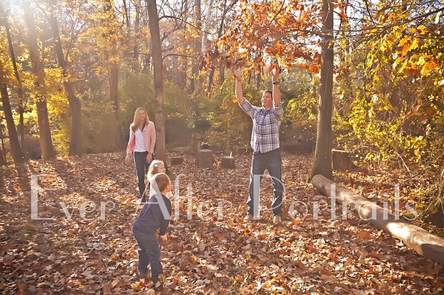 Family playing in leaves.