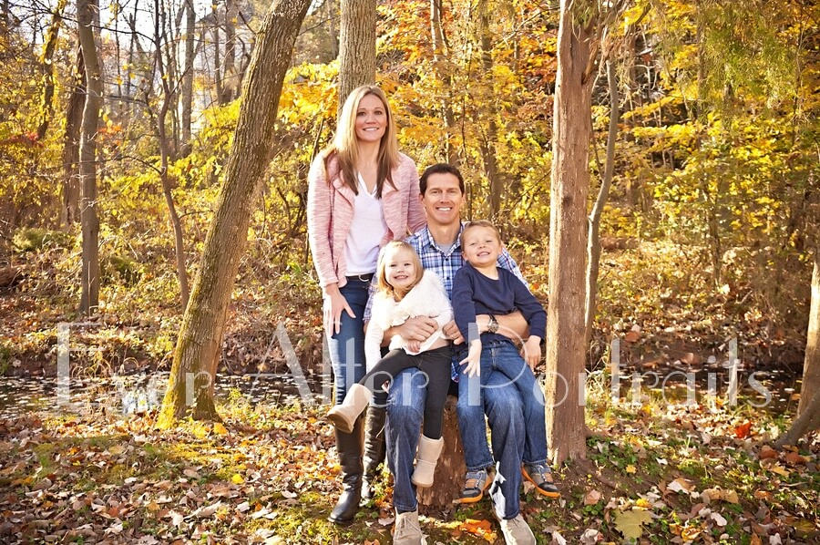 Family of four in autumn outdoor photo.