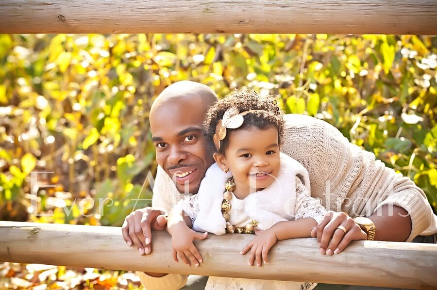 professional photographer Father with young daughter at fence.